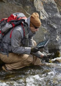 Man in outdoor protective, waterproof gear and backpack, kneeling in a mountain stream holding rocks in one hand and a Dell Latitude 12 Rugged Tablet (Model 7202) computer in the other.
